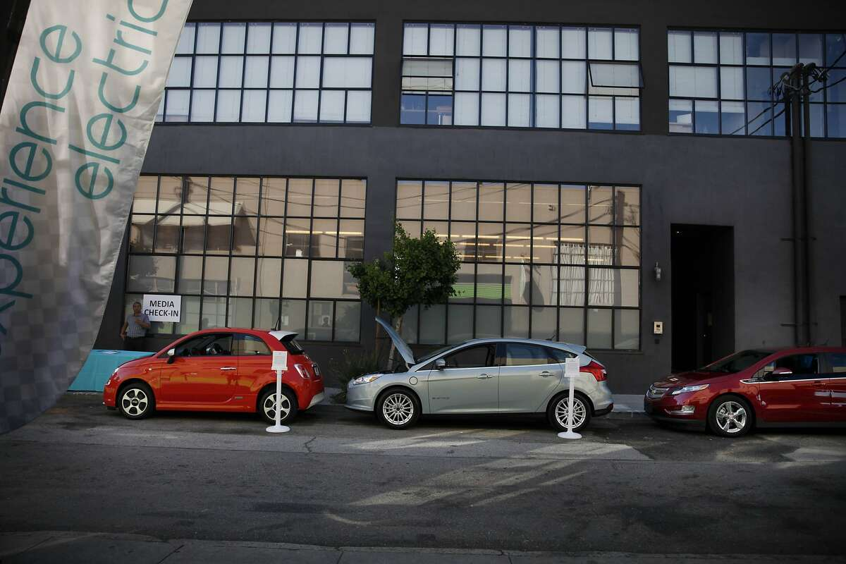 A Fiat 500e (l to r), a Ford Focus EV and a Chevrolet Volt are parked in a line during an event for