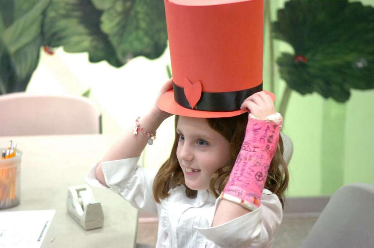 Charlotte Yehle, 7, tests out her Lincoln-esque top hat during the Bruce Museum's