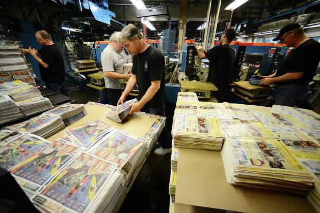 Jeff Blackman, center, and fellow Times Union mailroom workers, load coupon and ad materials into an inserter machine Thursday, May 15, 2014, at Times Union in Colonie, N.Y. (Will Waldron/Times Union) Photo: WW / 00026875A