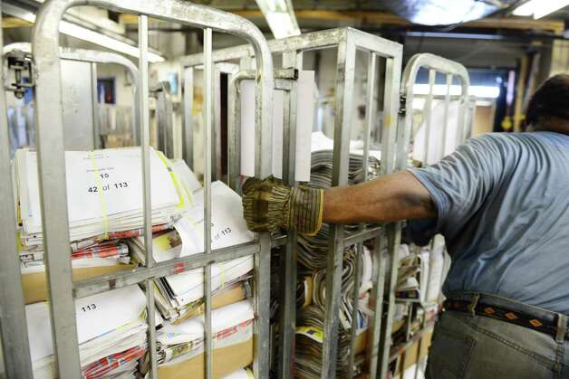 Times Union mailroom worker Doug Mackey moves bins of Times Union Saturday and Sunday supplement sections Thursday, May 15, 2014, at Times Union in Colonie, N.Y. (Will Waldron/Times Union) Photo: WW / 00026875A