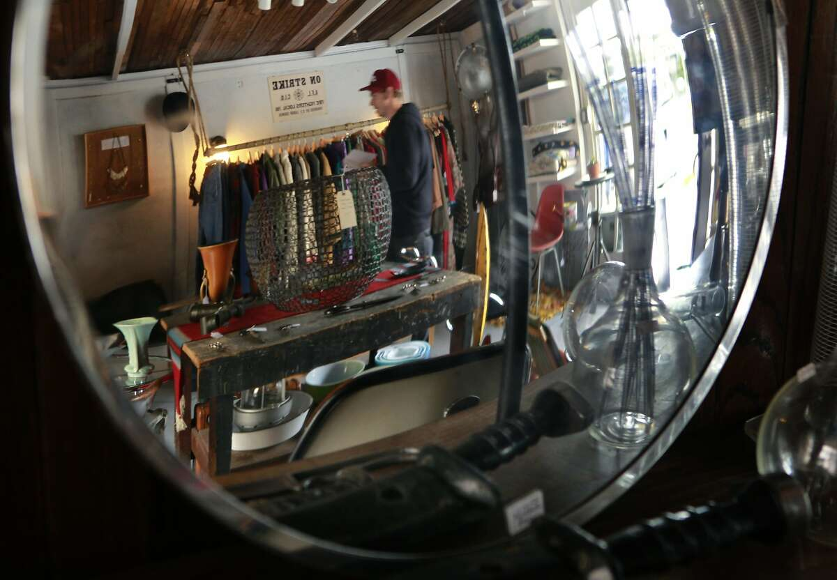 Co-owner Anthony Williamson arranges merchandise, which includes a wide angle mirror, at the new Mixed Nuts shop on Fell street in Hayes Valley in San Francisco, Calif. on Friday, April 11, 2014.