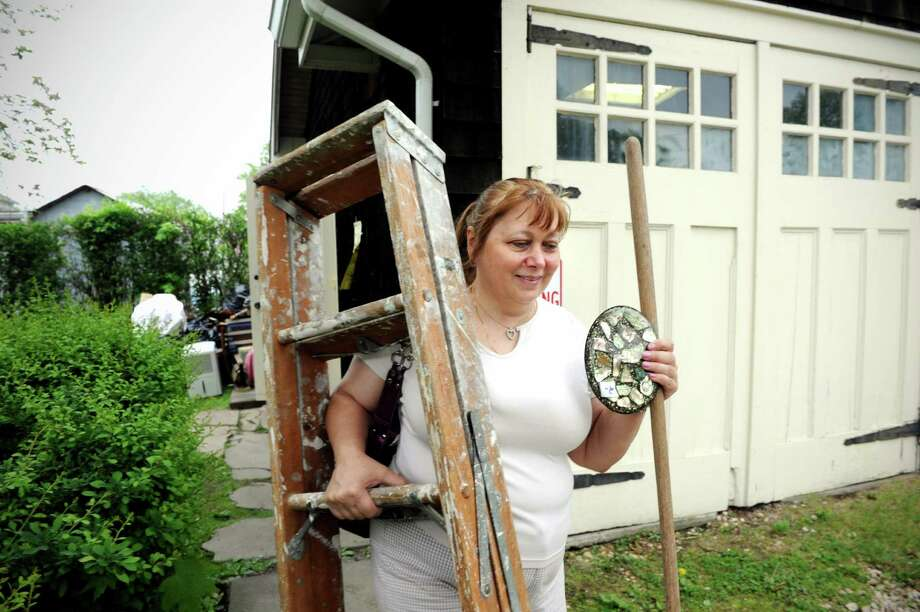 Laura Martin leaves a tag sale on West Broad St in Stamford, Conn. with a ladder and some other things she bought on Friday May 16, 2014. Photo: Dru Nadler / Stamford Advocate Freelance
