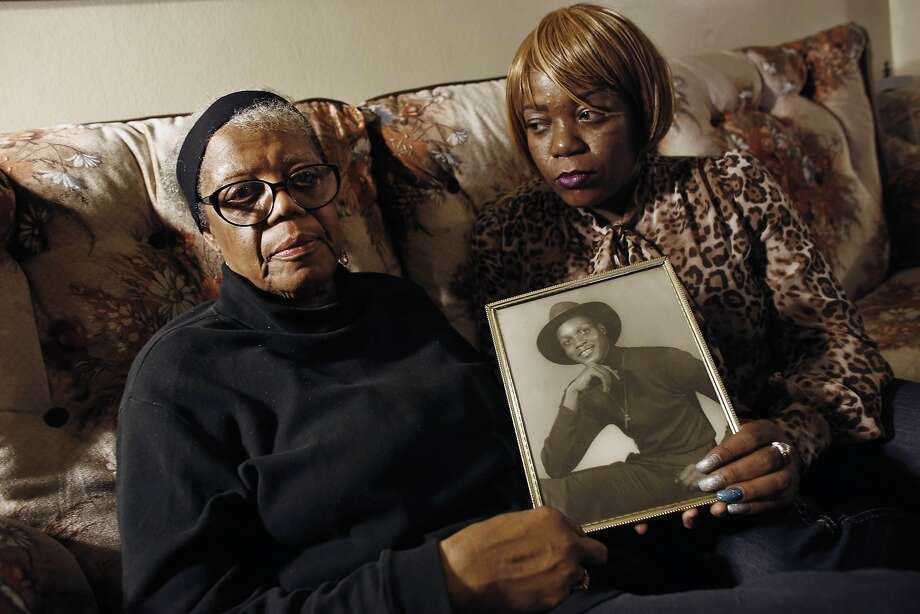 FILE- In this March 12, 2014 file photo, Alma Murdough and her daughter Cheryl Warner hold a photo of Murdough's son, at her home in the Queens borough of New York.  Jerome Murdough, a mentally ill, homeless former Marine arrested for sleeping in the roof landing of a New York City public housing project during one of the coldest recorded winters in city history, died in a Rikers Island jail cell that multiple city officials say was at least 100 degrees when his body was discovered. The former Marine will be buried in New Jersey on Friday, April 25, 2014, after a modest funeral service in the Queens borough of New York. (AP Photo/Jason DeCrow, File) Photo: Jason DeCrow, Associated Press