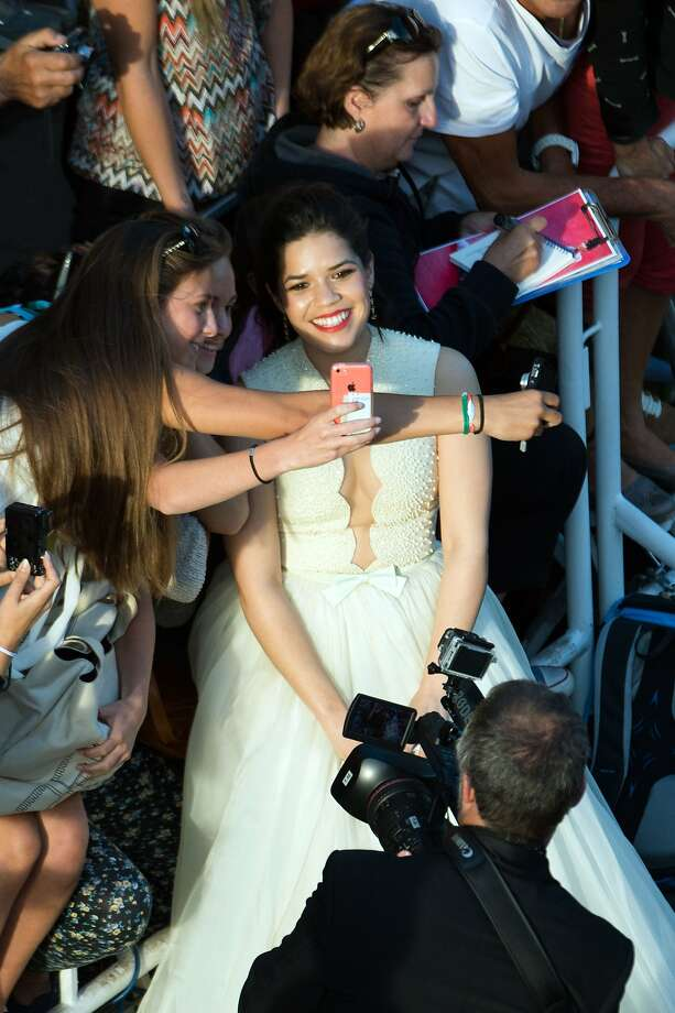 "Actress America Ferrera poses with fans as she arrives for the screening of the animated film ""How to train your Dragon 2"" at the 67th edition of the Cannes Film Festival in Cannes, southern France, on May 16, 2014. Photo: Bertrand Langlois, AFP/Getty Images"