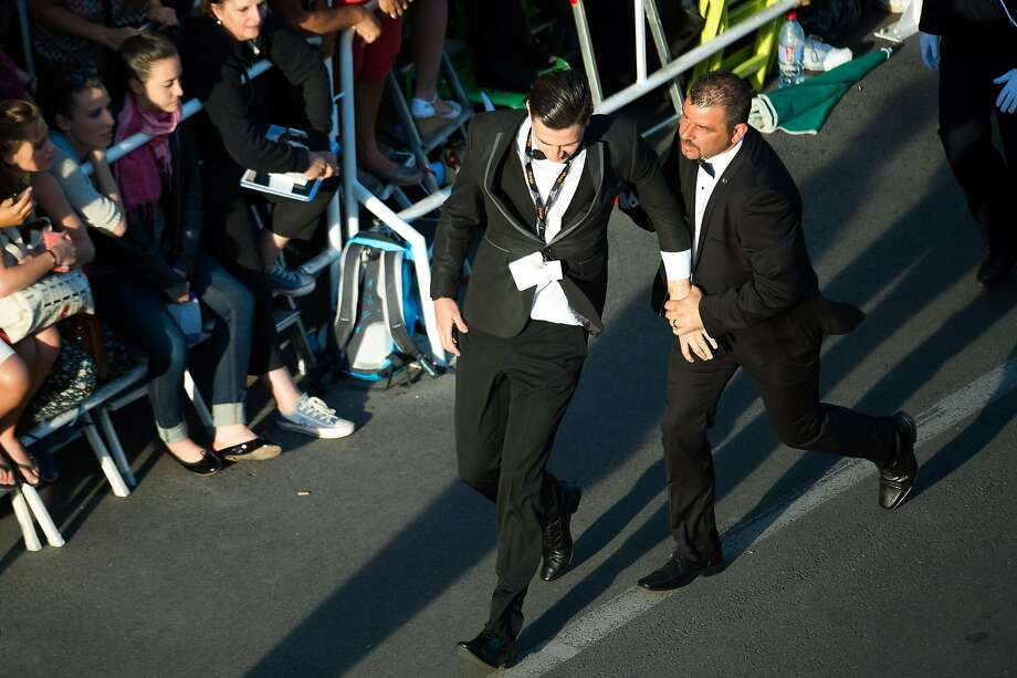 "An unidentified man is taken away by a minder after he tried to slip under US actress America Ferrera's dress as she arrived for the screening of the animated film ""How to train your Dragon 2"" at the 67th edition of the Cannes Film Festival in Cannes, southern France, on May 16, 2014. Photo: Bertrand Langlois, AFP/Getty Images"