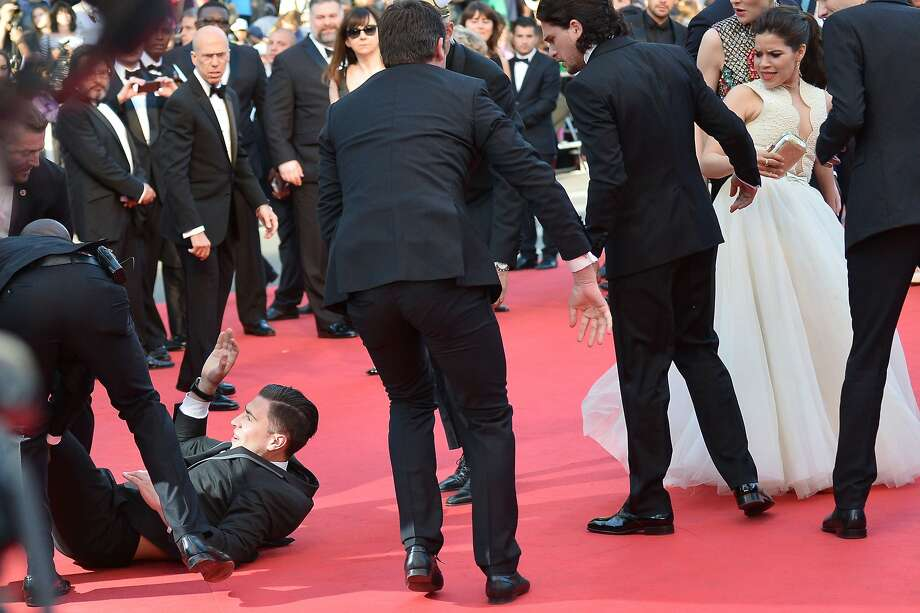 "An unidentified man is dragged away by minders after he tried to slip under US actress America Ferrera's dress (right) as she arrives for the screening of the animated film ""How to train your Dragon 2"" at the 67th edition of the Cannes Film Festival in Cannes, southern France, on May 16, 2014. Photo: Alberto Pizzoli, AFP/Getty Images"