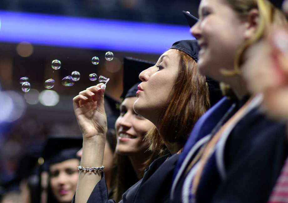 Natalie Parfitt, of Seymour, blows bubbles during Southern Connecticut State University's commencement ceremony Friday, May 16, 2014, at the Webster Bank Arena in Bridgeport, Conn. Photo: Autumn Driscoll / Connecticut Post