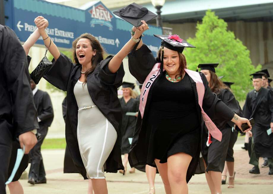 Friends Jennifer Meldon, of Brookfield, and Justine Konecky, of Naugatuck, right, hold hands as they enter into the Webster Bank Arena for the Southern Connecticut State University undergraduate commencement ceremony Friday, May 16, 2014, in Bridgeport, Conn. Photo: Autumn Driscoll / Connecticut Post