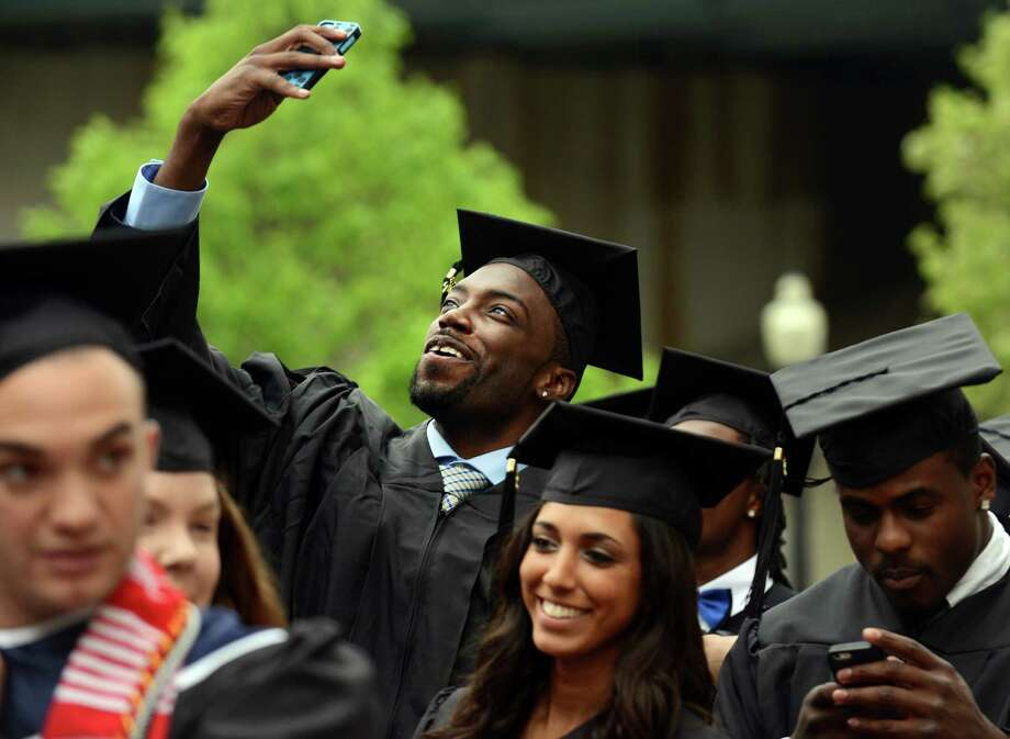 Trevon Hamlet, of Brooklyn, NY, takes a selfie as he lines up with other graduates before Southern Connecticut State University's commencement ceremony Friday, May 16, 2014, at the Webster Bank Arena in Bridgeport, Conn. Photo: Autumn Driscoll / Connecticut Post