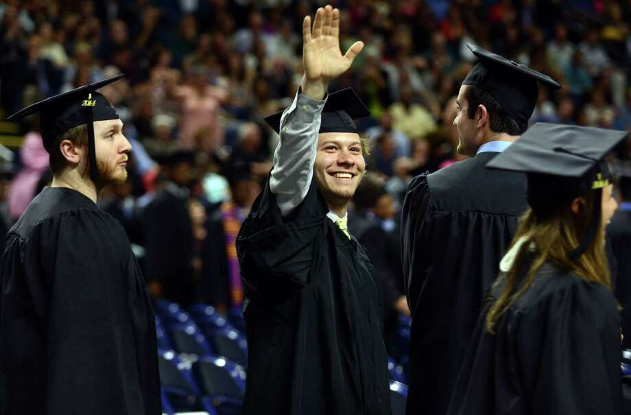 Keith Bennett, of Darien, waves to family in the stands as he lines up with other graduates before Southern Connecticut State University's commencement ceremony Friday, May 16, 2014, at the Webster Bank Arena in Bridgeport, Conn. Photo: Autumn Driscoll / Connecticut Post