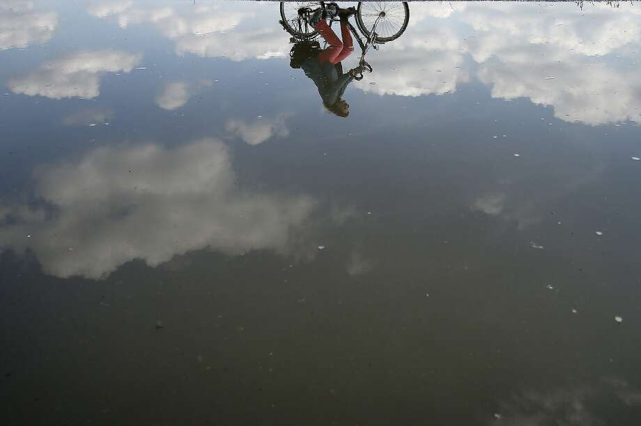 Pedaling in the clouds:A cyclist is reflected in a puddle left by a rainstorm in Duisburg, Germany. Photo: Frank Augstein, Associated Press