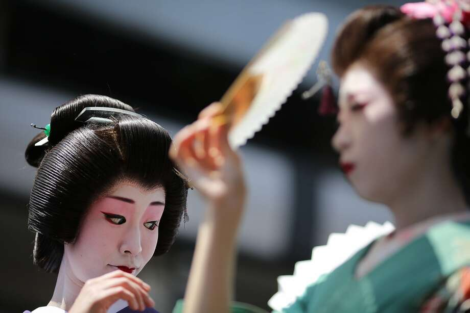 Geisha girls fan themselveswhile parading toward the Asakusa Shrine in the compound of Sensoji Temple in Tokyo. One 