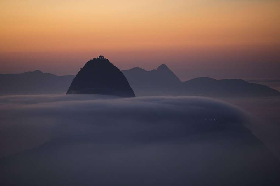 Oh, to live on Sugarloaf Mountain: Rio de Janeiro's famous landmark rises out of the early morning fog. Photo: Felipe Dana, Associated Press