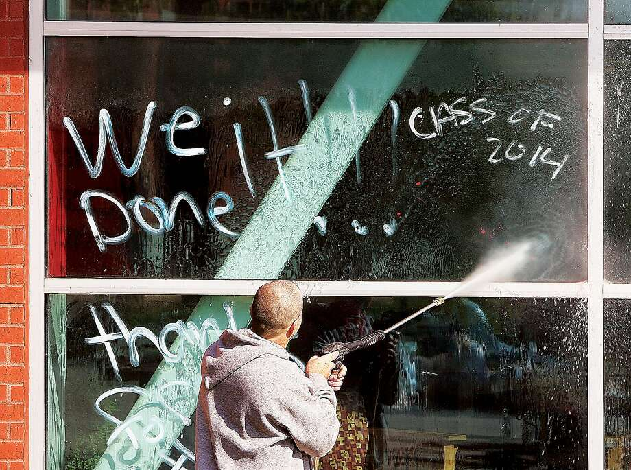 And by 'it,' we mean vandalism: An Alton, Ill., school district employee power-washes away the scrawled 