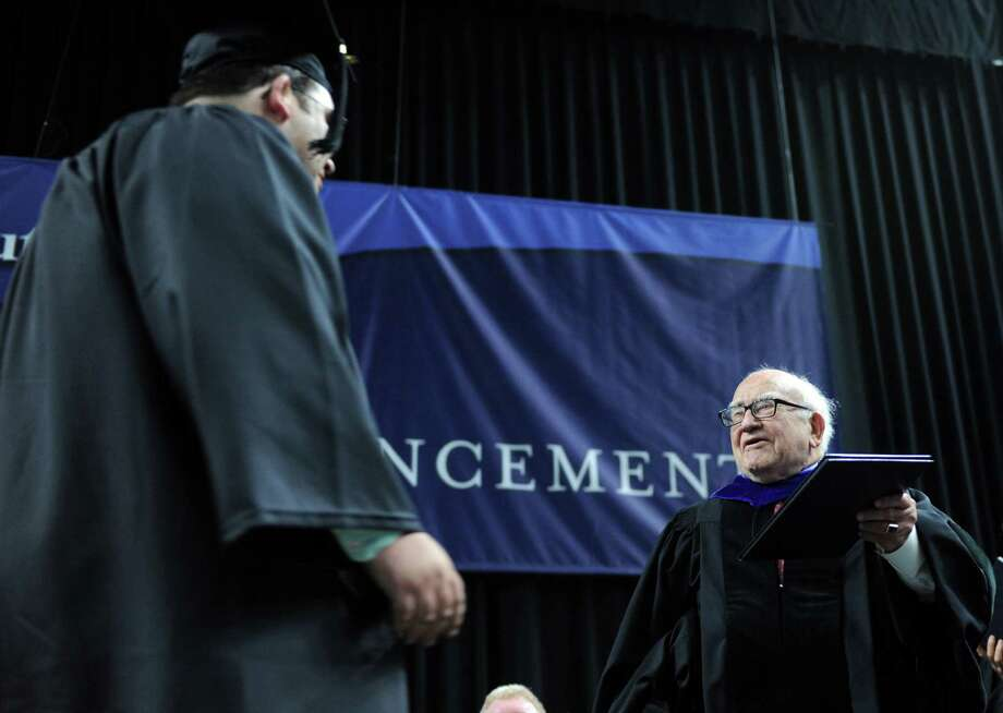 Edward Asner presents a diploma to his son Charles during Southern Connecticut State University's commencement ceremony Friday, May 16, 2014, at the Webster Bank Arena in Bridgeport, Conn. Photo: Autumn Driscoll / Connecticut Post