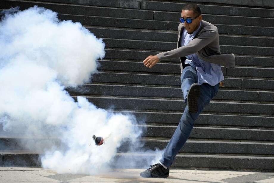 Gas, punt and kick: In Caracas, a demonstrator opposing the government of President Nicolas Maduro kicks a tear 