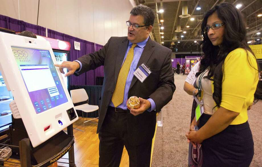 Chuck Olson, director of operations for CNC Vending, demonstrates a device to Angie Martinez of Benefits Solutions at the HR Houston symposium on human resource issues. His product completes food transactions with a touchscreen.  Photo: Billy Smith II, Staff