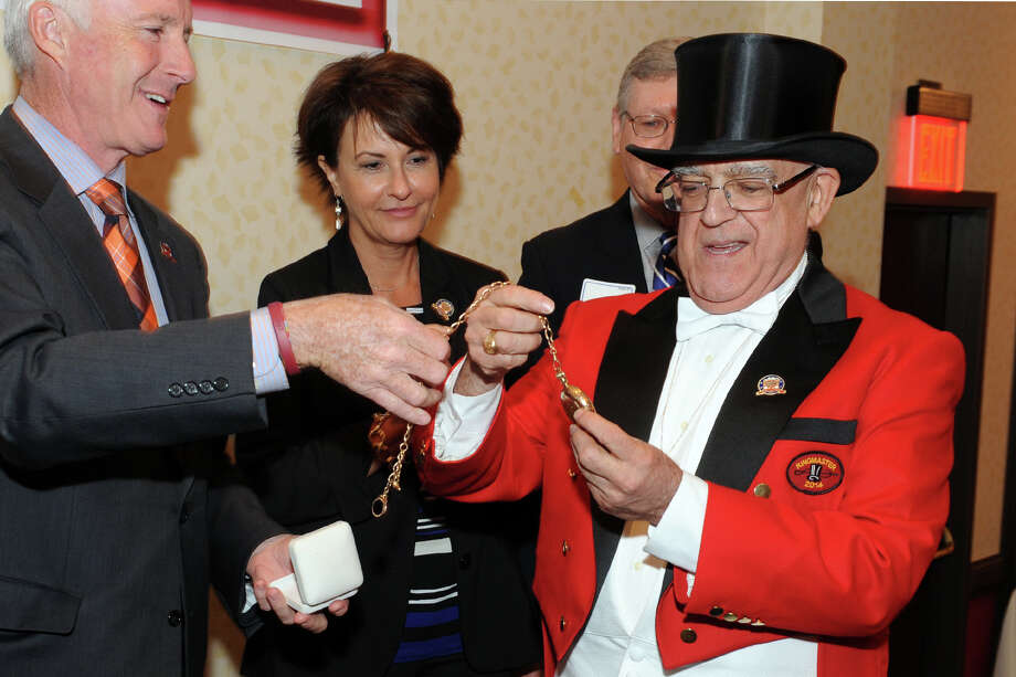 Bridgeport Mayor Bill Finch presents P.T. Barnum's gold watch to Paul Timpanelli, the 2014 Barnum Festival Ringmaster during the Whip, Whistle and Watch Luncheon, held at the Bridgeport Holiday Inn in Bridgeport, Conn. May 16, 2014. The annual luncheon is the inauguaral event of the Barnum Festival, which will conclude on June 29 with the Great Street Parade. Seen here with Timpanelli and Finch is Dianne Auger of St. Vincent's Health Services, one of the festival sponsors. Photo: Ned Gerard / Connecticut Post