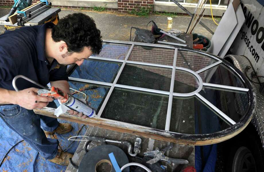 Marc Fritzer works on a window pane at Edmond Town Hall Friday.New windows are being installed in the Edmond Town Hall in Newtown, Conn., Friday, May 16, 2014. Because the building is an historic landmark extra steps are taken to preserve it authenticity as much as possible. Bi-Glass of Connecticut, specializing in restoring antique and historic windows has been hired to do the job. Photo: Carol Kaliff / The News-Times