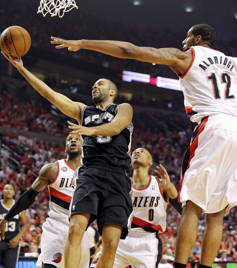 San Antonio Spurs' Tony Parker shoots between Portland Trail Blazers' Thomas Robinson (from left), Damian Lillard, and LaMarcus Aldridge during first half action of Game 3 in the Western Conference semifinals Saturday May 10, 2014 at the Moda Center in Portland, OR. Photo: Edward A. Ornelas, San Antonio Express-News