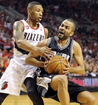 San Antonio Spurs' Tony Parker slips as he looks for room around Portland Trail Blazers' Damian Lillard during first half action of Game 3 in the Western Conference semifinals Saturday May 10, 2014 at the Moda Center in Portland, OR. Photo: Edward A. Ornelas, San Antonio Express-News
