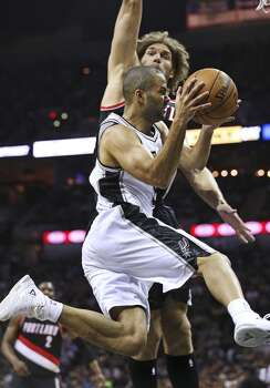 Tony Parker flies in under the hoop against Robin Lopez as the San Antonio Spurs play the Portland Trailblazers in game 2 of the Western Conference Semifinals at the AT&T Center on May 8, 2014. Photo: TOM REEL, San Antonio Express-News