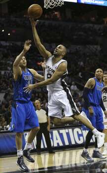 San Antonio Spurs' Tony Parker goes for two as Dallas Mavericks' Dirk Nowitzki defends during the first half of game seven in the first round of the Western Conference Playoffs at the AT&T Center, Sunday, May 4, 2014. Photo: Jerry Lara, San Antonio Express-News