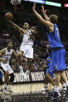 San Antonio Spurs' Tony Parker is fouled by Dallas Mavericks' Vince Carter while attacking the goal during the first half of game seven in the first round of the Western Conference Playoffs at the AT&T Center, Sunday, May 4, 2014. Photo: Jerry Lara, San Antonio Express-News