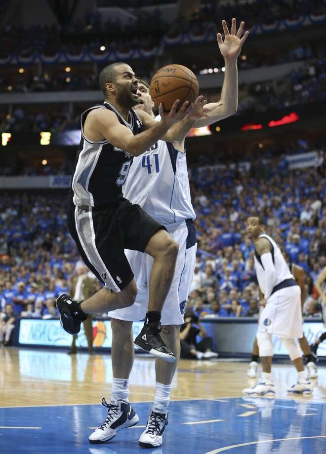 San Antonio Spurs' Tony Parker drives to the goal as Dallas Mavericks' Dirk Nowitzki defends during the second half of game six in the first round of the Western Conference Playoffs at the American Airlines Center in Dallas, Friday, May 2, 2014. The Mavericks won 113-111 to even the series at 3-3. Photo: Jerry Lara, San Antonio Express-News