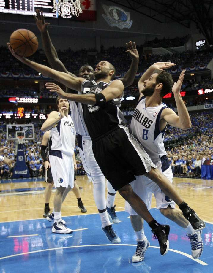San Antonio Spurs' Tony Parker goes under the basket as Dallas Mavericks' Jose Calderon defends during the first half of game six in the first round of the Western Conference Playoffs at the American Airlines Center in Dallas, Friday, May 2, 2014. The Mavericks won 113-111 to even the series at 3-3. Photo: Jerry Lara, San Antonio Express-News