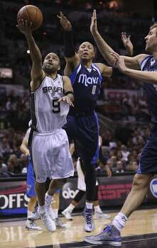 San Antonio Spurs' Tony Parker goes for the goal as Dallas Mavericks' Shawn Marion and Dirk Nowitzki defend during the first half of game five in the first round of the Western Conference Playoffs at the AT&T Center, Wednesday, April 30, 2014. Photo: Jerry Lara, San Antonio Express-News