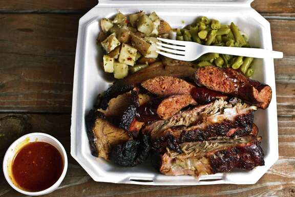Brooks Place BBQ's three meat plate, sliced beef, pork ribs and sausage link.