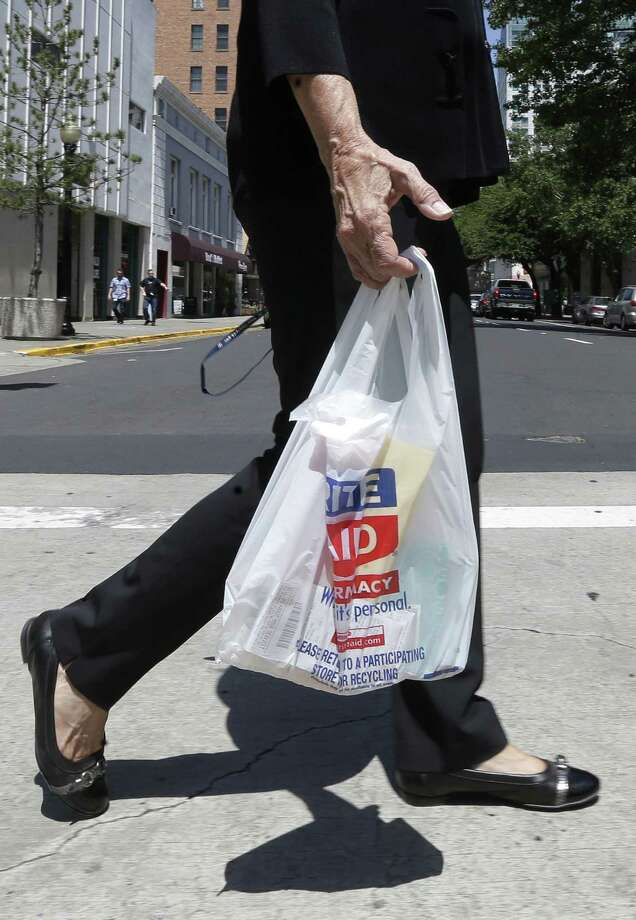 A woman walks with a plastic bag in Sacramento, California. A bill to make California the first in the nation to impose a statewide ban on plastic bags seems to be on track. An Express-News reader touts a similar ban, saying she prefers reusable bags. Photo: Associated Press / AP
