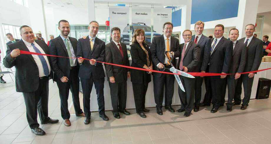 Left to right are Matthew O'Brist, DeMontrond Volkswagen general sales manager; Arin Booth, VCI, senior manager Sales Operations; Jerritt Park, VCI, Business Development manager; Mike Sandler, Volkswagen Fixed Operations general manager; Marilyn DeMontrond; George A. DeMontrond III, owner/dealer principal; Reggie Gray, Houston Intercontinental Chamber of Commerce president; Ron Stach, Volkswagen Regional director; David Latta, DeMontrond general manager; Rich Henderson, Volkswagen Sales Operations manager; and Scott Bell, VCI Regional director, helping with the ribbon cutting at the grand opening of DeMontrond Volkswagen facility.