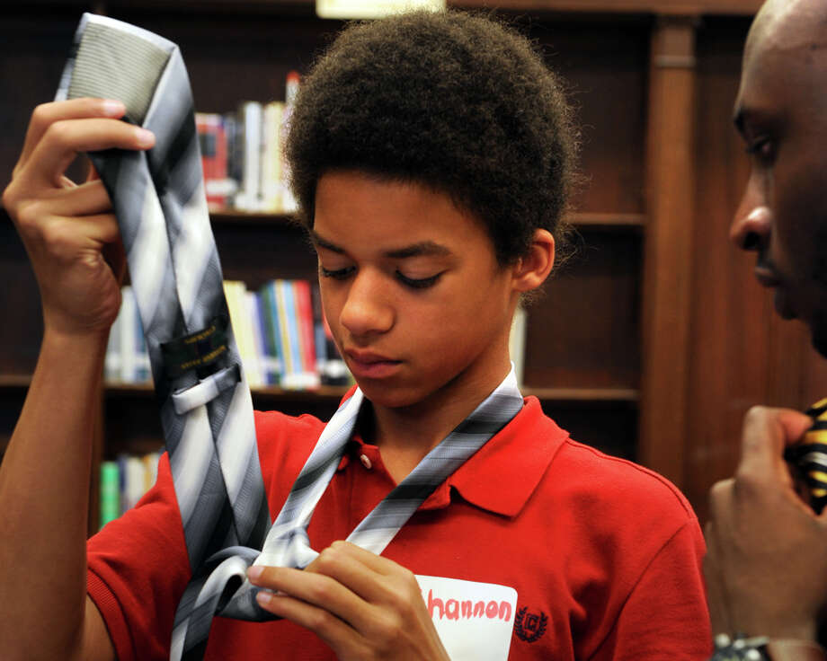 "Shannon Parks, a freshman at Harding High School, makes his first attempt at tying a neck tie with the guidance of D.J. Ellis, a mentor with the ""Becoming a Pro"" program, in Bridgeport, Conn. May 16, 2014. The program introduced male students at the school to the concepts of positive and professional self identity and charactor. Photo: Ned Gerard / Connecticut Post"