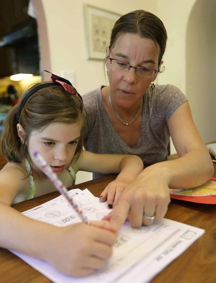 Stacey Jacobson-Francis works on math homework with her 6-year-old daughter Luci at their home in Berkeley. Photo: Associated Press