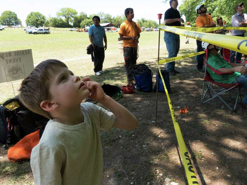 Topher Nelson, 6, watches as climbers compete in the 2014 Texas Tree Climbing Championship in New Braunfels on Friday, May 16, 2014. The International Society of Arboriculture (ISA) Tree Climbing Championship tests the competitors' ability to safely maneuver in a tree while performing work. Events include the throw line, foot lock, aerial rescue and work climb.