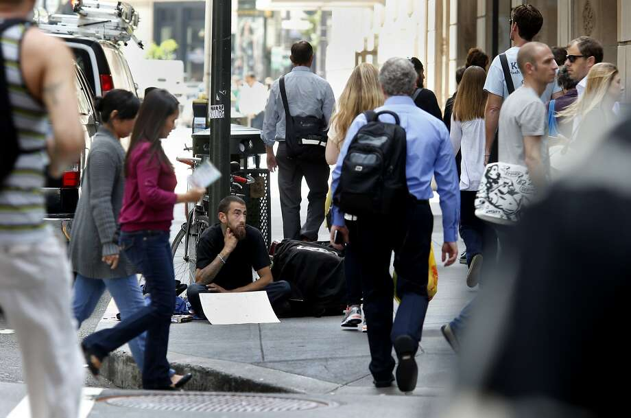 On Montgomery Street, a man asking for money watches people as they crowd the street and sidewalk Thursday May 15, 2014 in San Francisco, Calif. The San Francisco Human Services Agency has put out a report about income inequality which is growing at a startling pace, where the rich are getting richer and the poor are getting poorer. The middle class seem to be leaving. Photo: Brant Ward, The Chronicle
