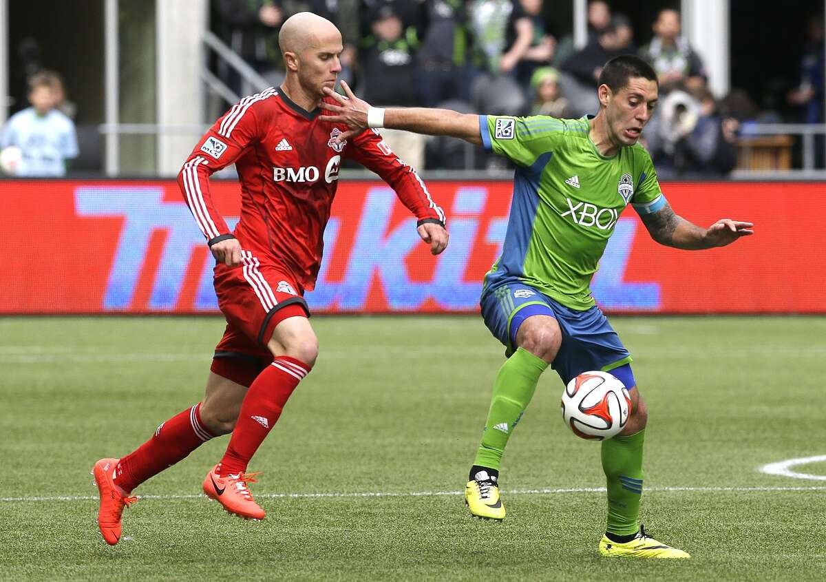 Seattle Sounders' Clint Dempsey, right, tries to hold off Toronto FC's Michael Bradley, left, in the second half of an MLS soccer match on Saturday, March 15, 2014, in Seattle. Toronto won 2-1. (AP Photo/Ted S. Warren)