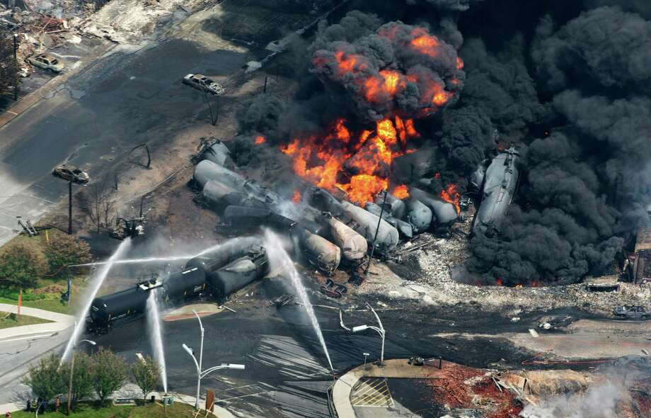 FILE - In this July 6, 2013 photo, smoke rises from flaming railway cars that were carrying crude oil after it a train derailed in downtown Lac Megantic, Quebec, Canada. A large swath of the town was destroyed after the derailment, sparking several explosions and fires that claimed 47 lives. John Giles, top executive of Central Maine and Quebec Railway, that purchased the railroad responsible for the derailment, said Friday, May 16, 2014 that they plan to resume oil shipments after track safety improvements are made. (AP Photo/The Canadian Press, Paul Chiasson, File) ORG XMIT: BX116 Photo: Paul Chiasson / The Canadian Press