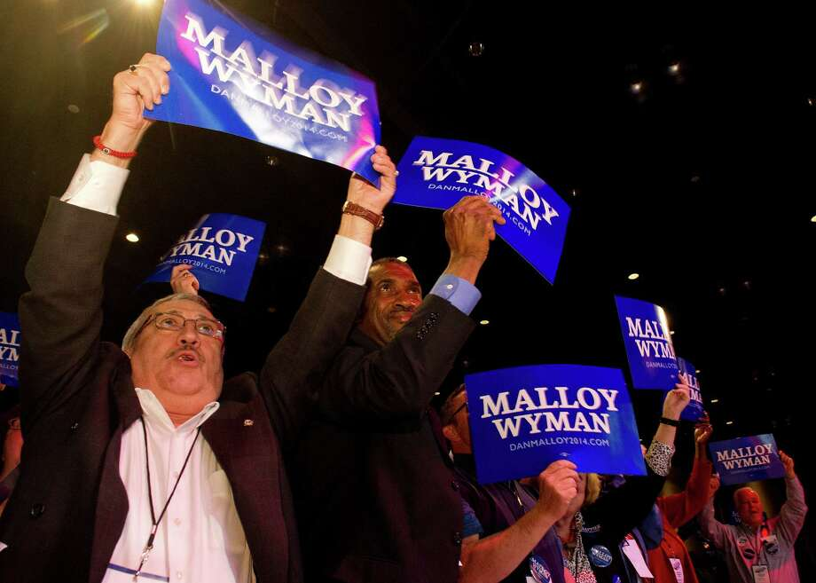 The Stamford delegation, including Willy Giraldo, left, and Terry Adams, right, cheers for Dannell Malloy during the Connecticut Democratic Convention in Hartford, Conn., on Friday, May 16, 2014. Photo: Lindsay Perry / Stamford Advocate