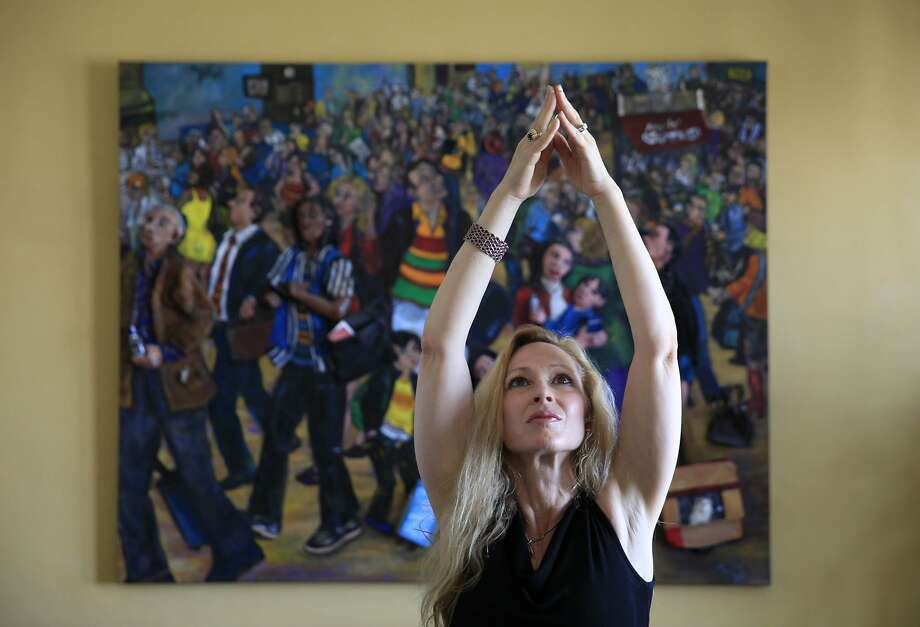 "Artist Nancy Calef, who is releasing her illustrated memoir, ""Peoplescapes: My Story from Purging to Painting,"" holds a yoga position in front of one of her artworks. Calef says creativity is a key to recovering from traumas. Photo: Lea Suzuki, The Chronicle"