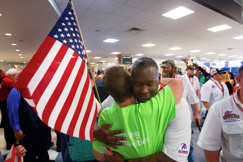 "Carolyn Suydam, left, hugs Wounded Warrior Robert Dawsey, right, after he arrived with other wounded warriors at George Bush International Airport, Friday, May 16, 2014, in Houston. The arrival of the wounded veterans kicks off the beginning of ""Warrior Weekend,"" a project of the Wounded Warrior Organization, in which wounded veterans participate in a deep-sea fishing trip in Port O'Connor. ""I love this, they truly are my heroes,"" she said. ""They are the heart and spirit of our nation."" Photo: Cody Duty, Houston Chronicle / © 2014 Houston Chronicle"