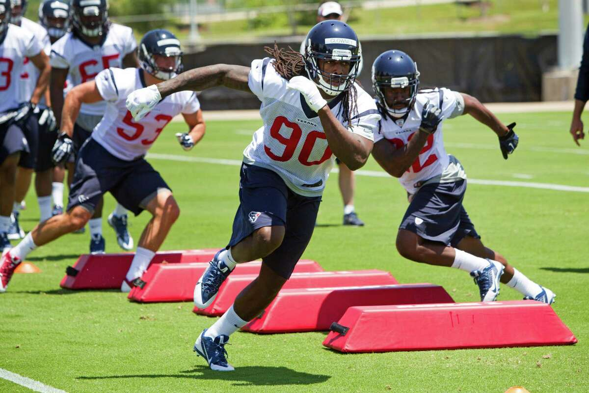 Top draft pick Jadeveon Clowney (90) gets his feet wet as a pro by running through a drill at the Texans rookie minicamp Friday.