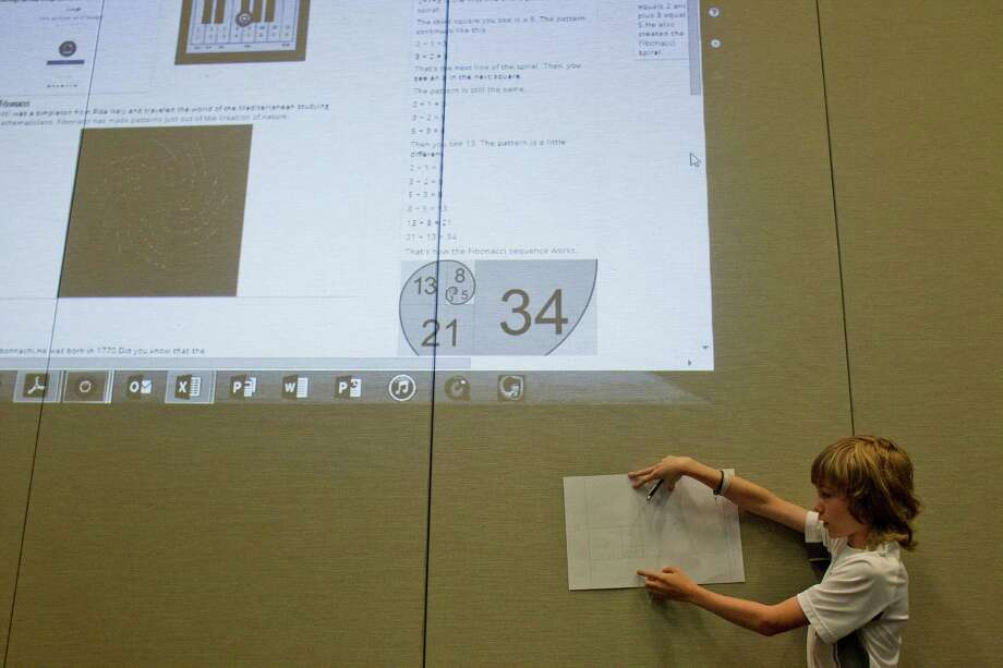 Ben Sandlin, 12, presents his findings after the class researched Leonardo Fibonacci and the Fibonacci Sequence during class at the A+ Unlimited Potential school held at The John P. McGovern Museum of Health and Medical Science Friday, May 9, 2014, in Houston. Photo: Johnny Hanson, Houston Chronicle / © 2014  Houston Chronicle