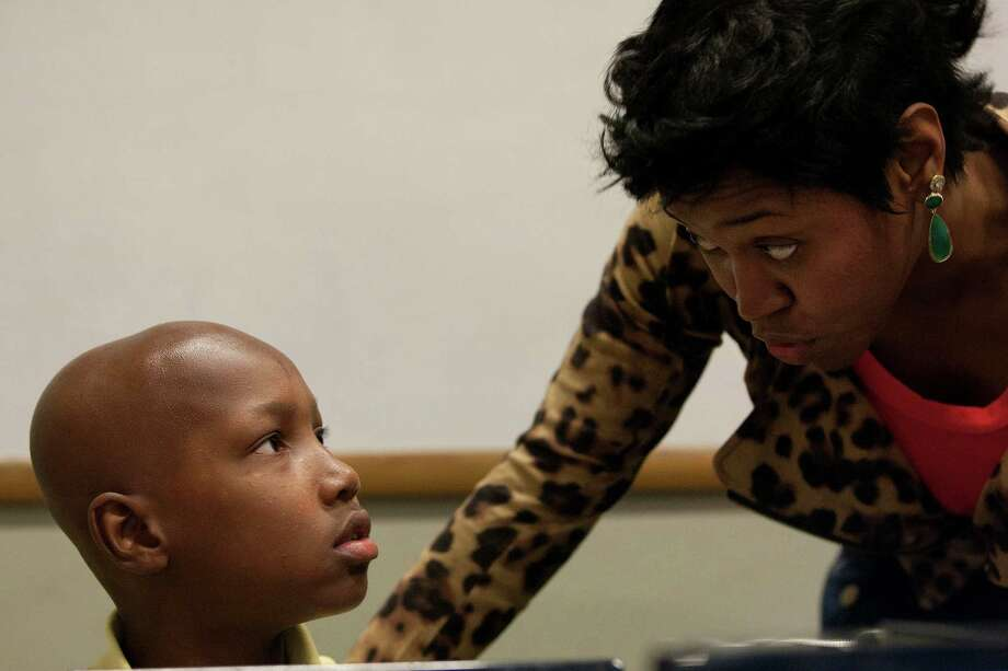 Sixth-grader, Thaddeus Wordlaw, 11, listens to instruction from learning coach, Cicely Benoit, as the class researched the Fibonacci Sequence and how the sequence applied to real life. Photo: Johnny Hanson, Houston Chronicle / © 2014  Houston Chronicle