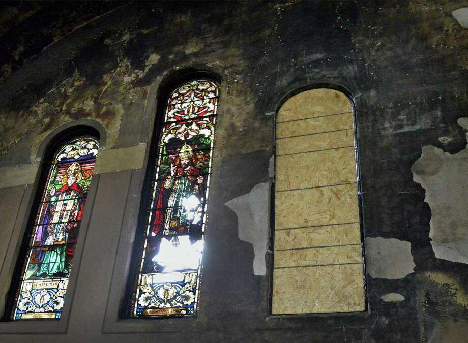 Fire damage can be seen in the stained glass windows above the altar in the sanctuary of St. Anthony's Church Friday May 16, 2014, in Schenectady, NY.  (John Carl D'Annibale / Times Union) Photo: John Carl D'Annibale / 00026925A
