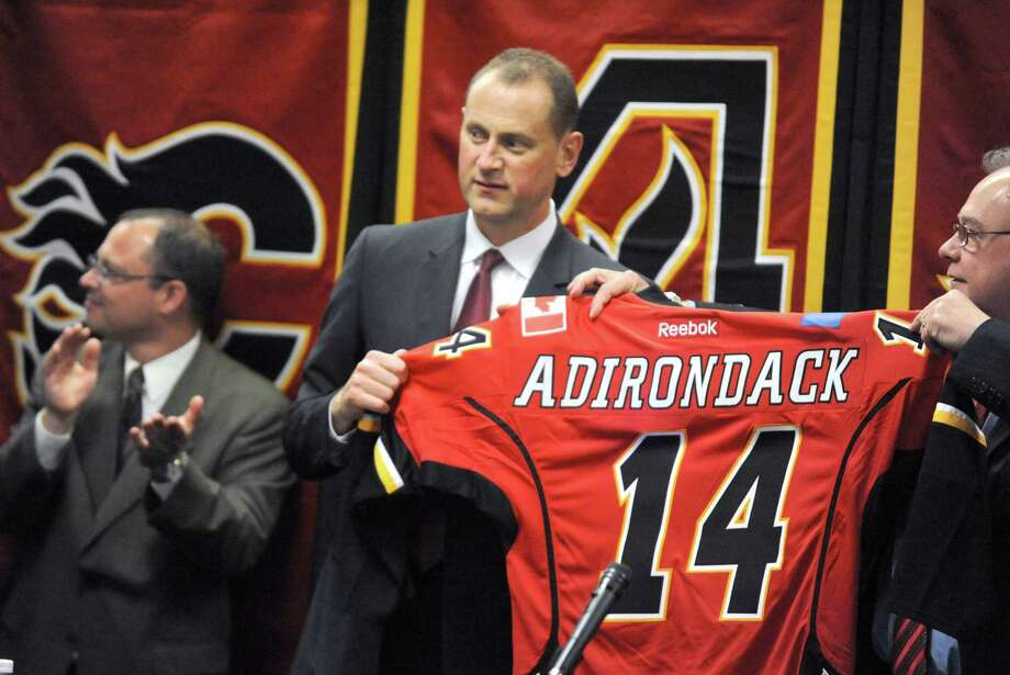Calgary Flames general manager Brad Treliving, center, and Glens Falls Mayor Jack Diamond hold up the AHL Adirondack Flames jersey during a press conference to announce the team will be calling the Glens Falls Civic Center it's new home on Friday May 16, 2014 in Glens Falls, N.Y. (Michael P. Farrell/Times Union) Photo: Michael P. Farrell / 00026913A