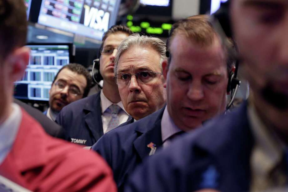 Traders' expressions on the floor of the New York Stock Exchange on Friday ranged from dour to sour. Uneven trading on Wall Street may indicate that many Americans, still haunted by the financial crisis, don't trust the recovery. Photo: Richard Drew, STF / AP