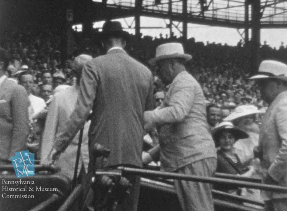 In this image taken from film shot by former Major League Baseball player Jimmie DeShong and acquired by the Pennsylvania Historical & Museum Commission, President Franklin D. Roosevelt, center right, walks to his seat with the aid of an assistant at the Major League Baseball All-Star game on July 7, 1937 at Griffith Stadium in Washington. The rare footage helps dispel the myth that he tried to hide his disability and shows the courage it took to go about his daily life, experts said Friday, May 16, 2014. (AP Photo/Pennsylvania Historical & Museum Commission) ORG XMIT: NY113